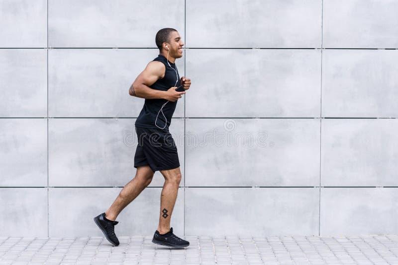 Афро-американский спортсмен бежать на улице стоковое фото rf