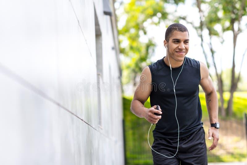 Афро-американский спортсмен бежать на улице стоковое фото