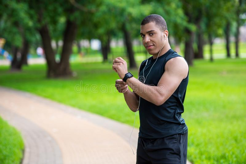 Афро-американский спортсмен используя smartwatch стоковое фото rf
