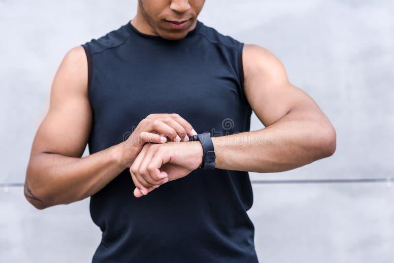 Афро-американский спортсмен используя smartwatch стоковые изображения