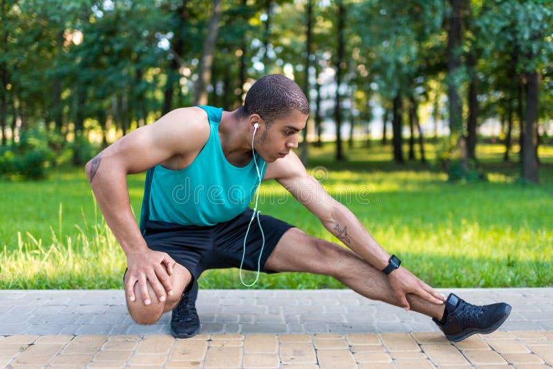 Афро-американский спортсмен протягивая в парке стоковые изображения