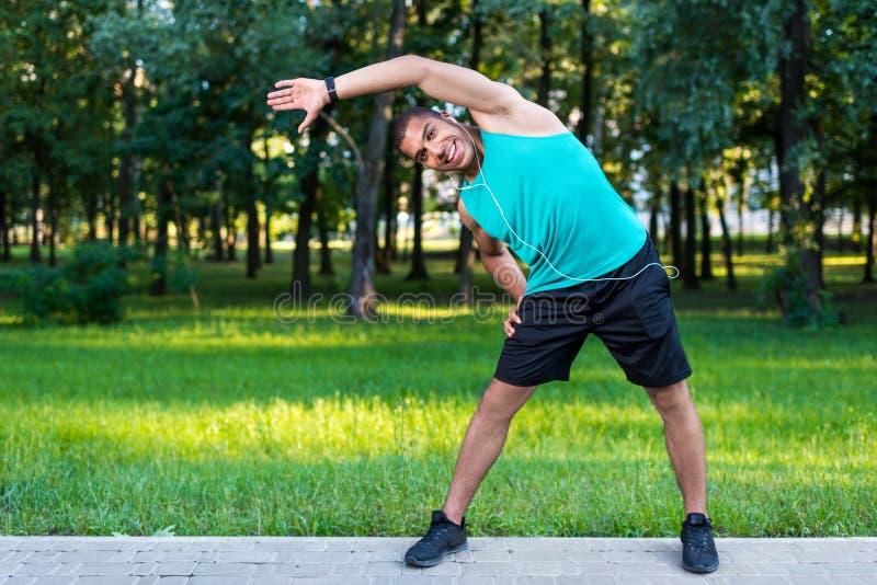 Афро-американский спортсмен протягивая в парке стоковые изображения rf