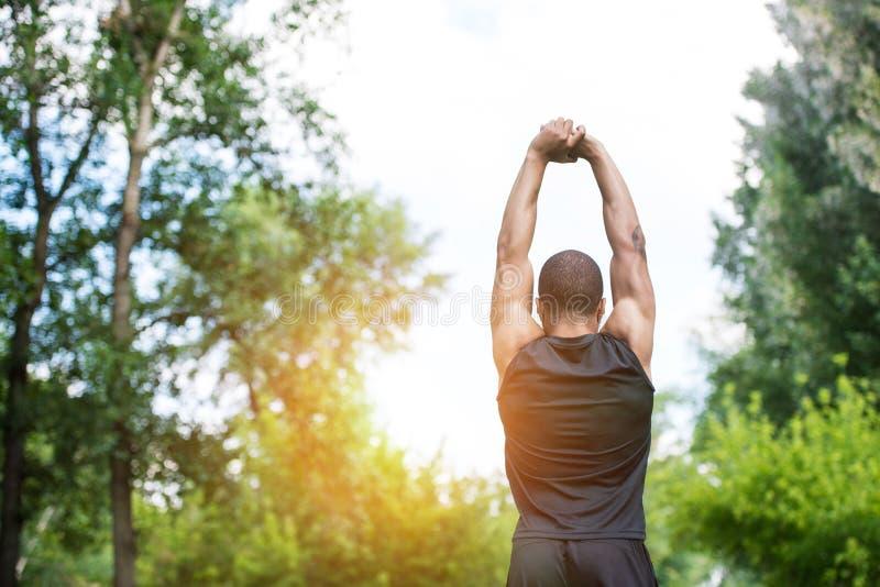 Афро-американский спортсмен протягивая в парке стоковая фотография