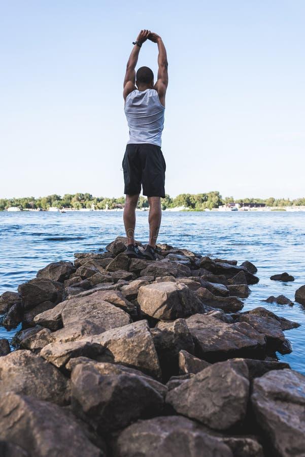 Афро-американский спортсмен протягивая на береге реки стоковые фото