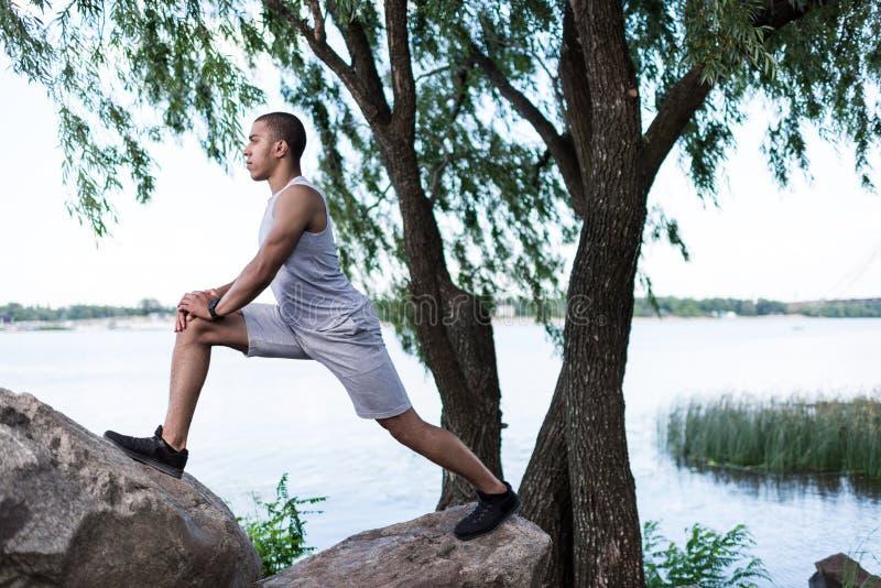 Афро-американский спортсмен протягивая на береге реки стоковая фотография rf