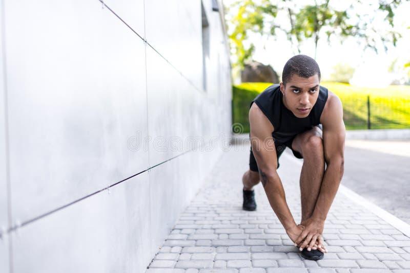 Афро-американский спортсмен протягивая на улице стоковое изображение rf