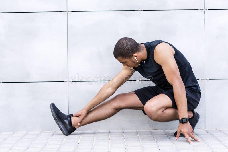 Афро-американский спортсмен протягивая на улице стоковая фотография rf