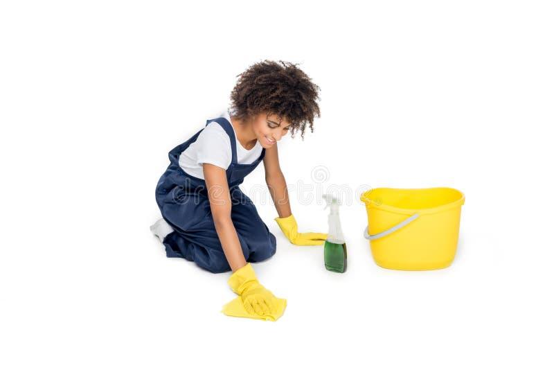 Афро-американский уборщик в равномерном tidying поле с cleanser и сыпней стоковое изображение