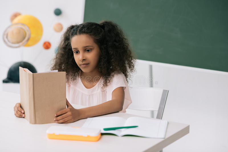 Афро-американский учебник чтения школьницы в классе стоковая фотография