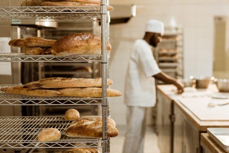 Афро-американский хлебопек подготавливая сырцовое тесто на рабочем месте с полками свежих ломтей хлеба стоковая фотография