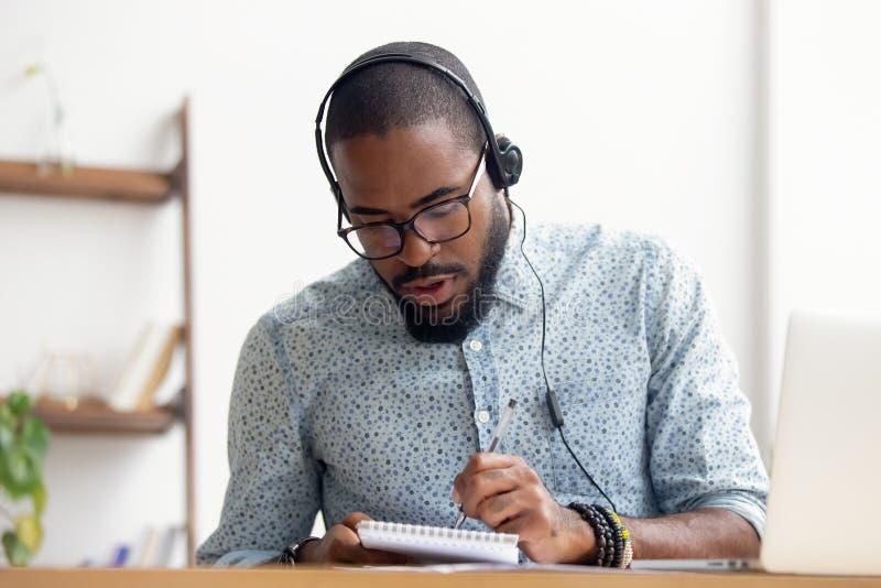 Афро-американский человек в наушниках принимая курс обучения по Интернету на офис стоковое изображение