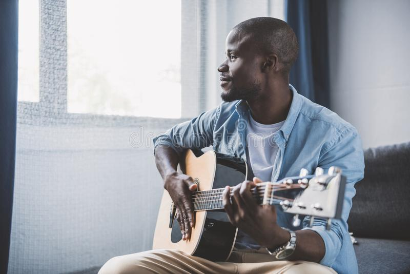 Афро-американский человек играя акустическую гитару стоковое изображение rf