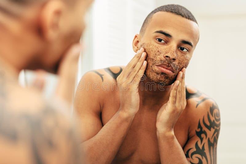 Афро-американский человек прикладывая косметику scrub сливк стоковое изображение
