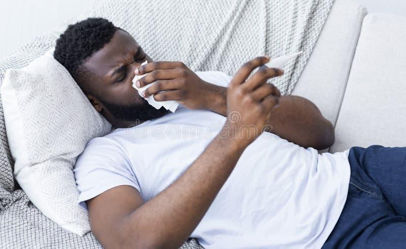 Афро-американский человек человека имеет жидкий нос дома стоковое изображение rf