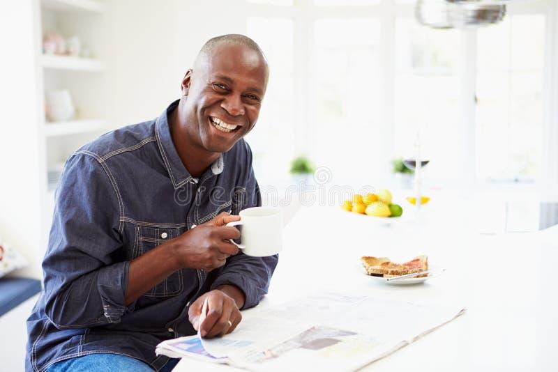 Афро-американский человек есть завтрак и читая газету стоковое фото rf