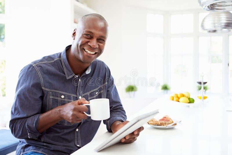 Афро-американский человек используя таблетку цифров дома стоковые фото