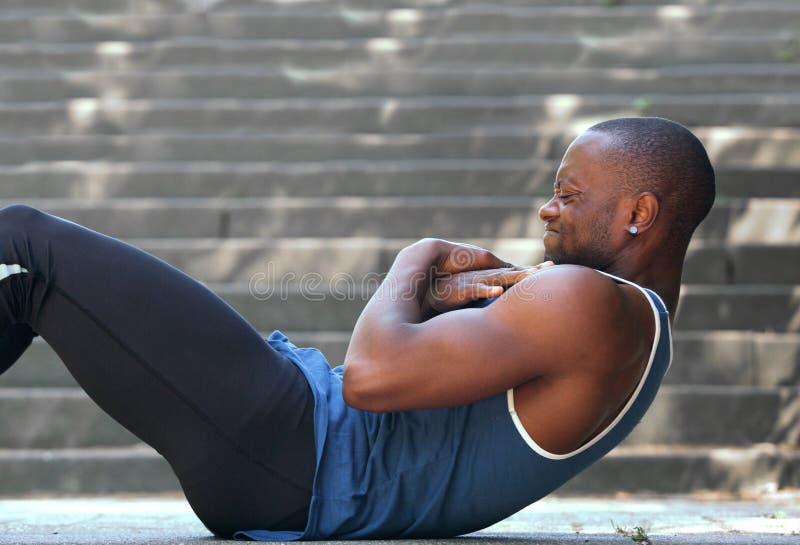 Афро-американский человек разминка тренировки спорта сидит поднимает снаружи стоковое фото