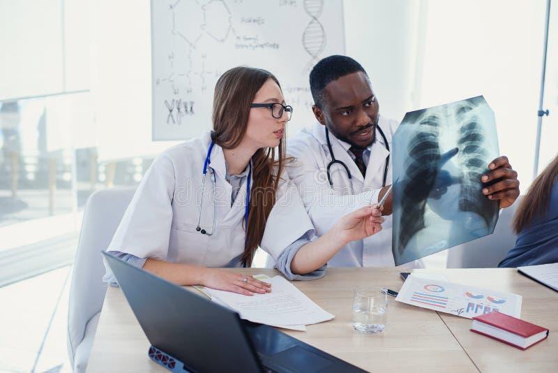 Афро американское и кавказские доктора в белых медицинских формах рассматривая рентгеновские снимки пациента на конференц-зале в  стоковые изображения rf