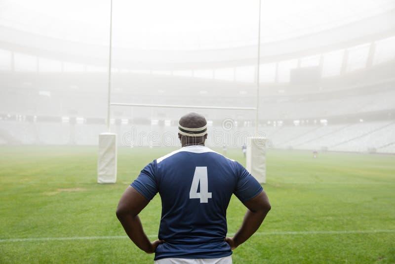 Афро-американское мужское положение игрока рэгби с руками на бедре в стадионе стоковые фото