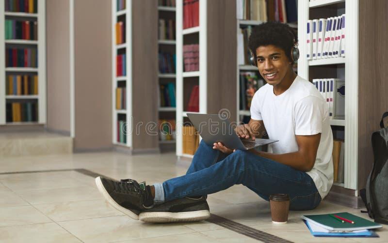 Афро-студент слушает музыку во время учебы, сидит на полу стоковая фотография rf
