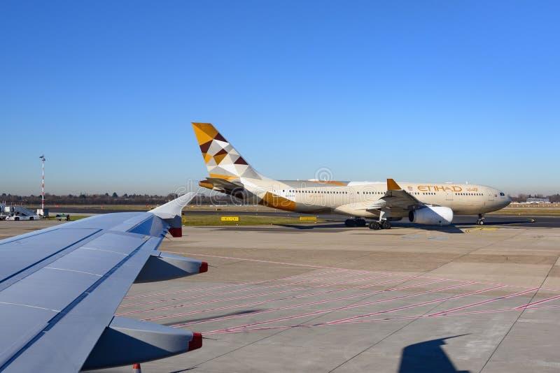 Аэробус A330-243 авиакомпании Etihad на земле аэропорта Самолет ирландской авиакомпании Ryanair стоковое фото