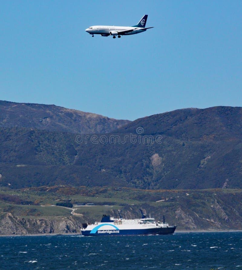 Аэроплан на конечном заходе к аэропорту Веллингтона, пропускам над паромом Interislander на ем путь к южному острову на поваре стоковые изображения