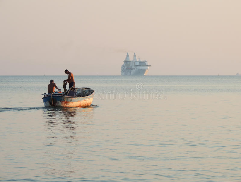 Албанские рыболовы в их старой рыбацкой лодке, большой современный корабль в расстоянии стоковая фотография