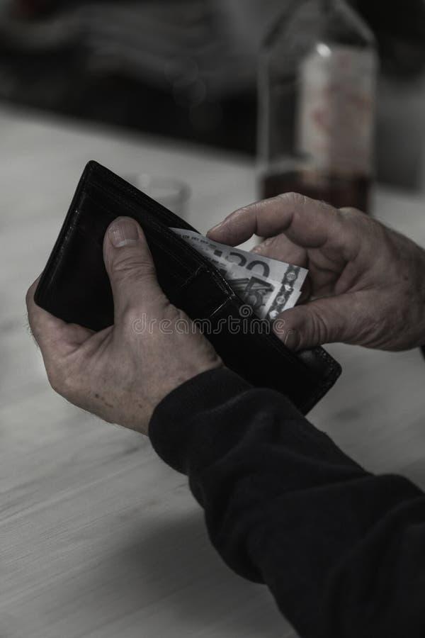 Алкоголичка тратит его пенсию для питья стоковое фото rf
