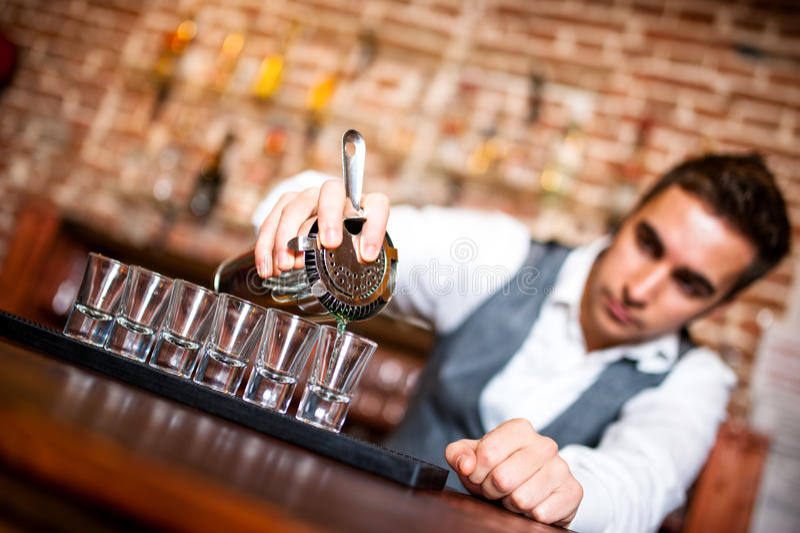 Алкогольный напиток бармена лить в малые стекла на баре стоковые изображения rf