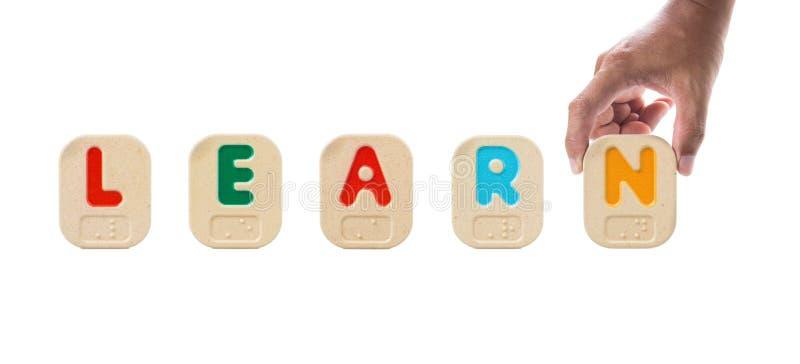 Алфавит преграждает говорить слово по буквам УЧИТ с Шрифтом Брайля стоковые фото