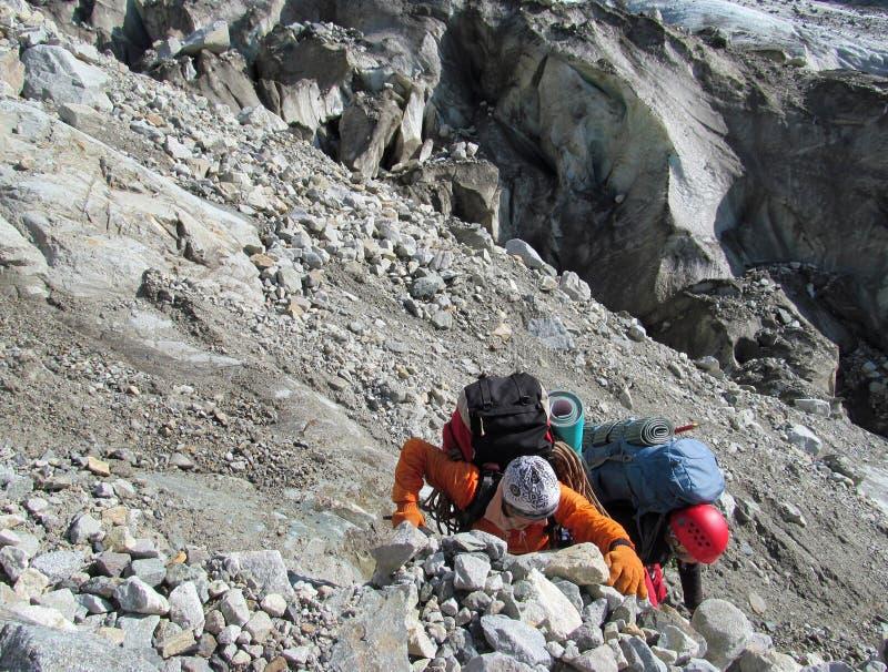 Альпинисты взбираясь скалистая гора стоковое изображение