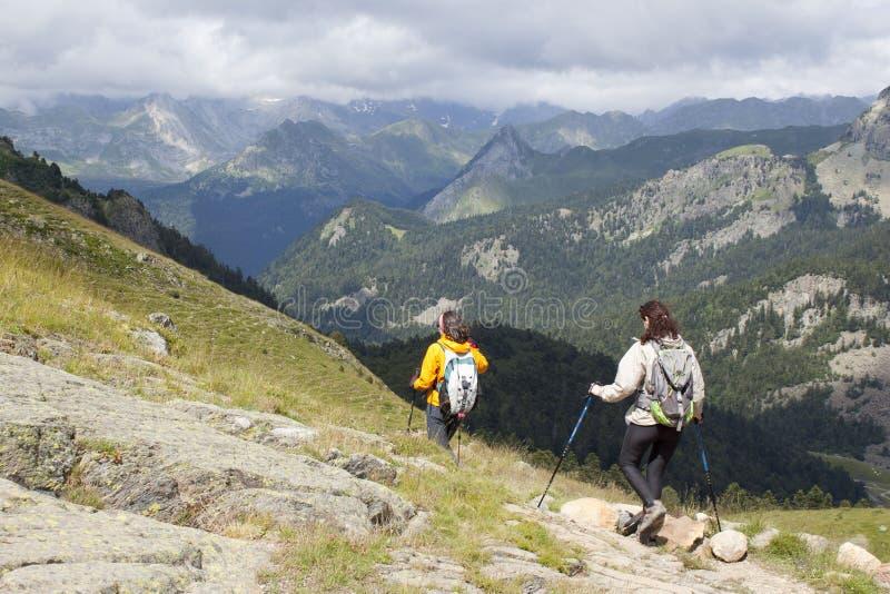 Альпинисты идя вниз с гор в отклонении стоковое изображение rf