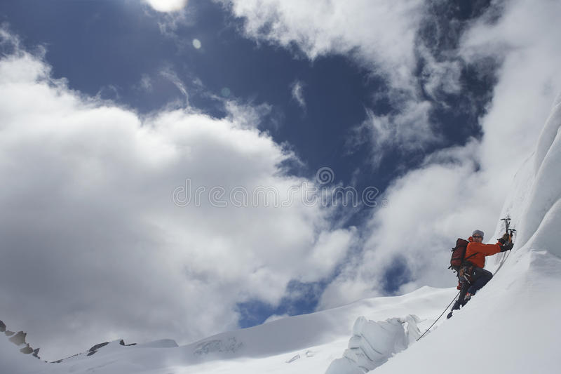 Альпинист идя вверх наклон Snowy с осями стоковые изображения rf