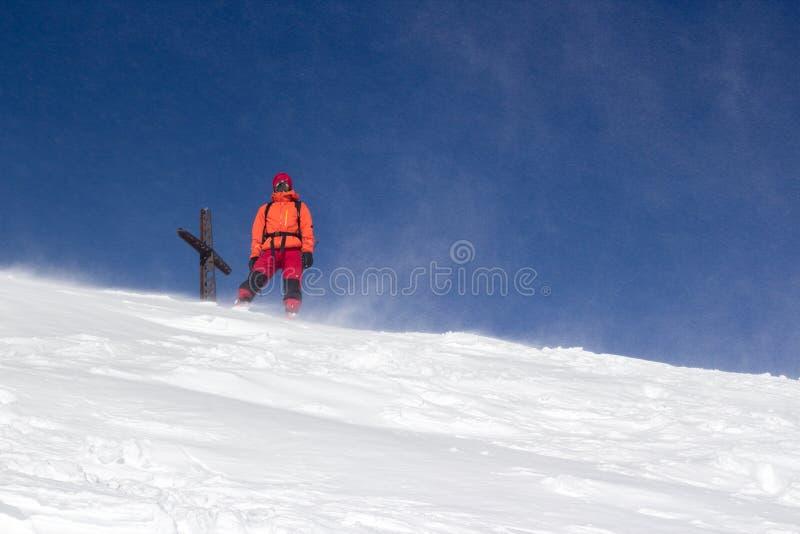 Альпинист стоя в верхней части идти снег peack стоковые изображения