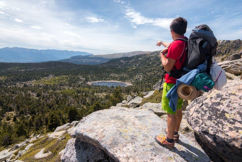 Альпинист указывая крошечное озеро стоковые изображения
