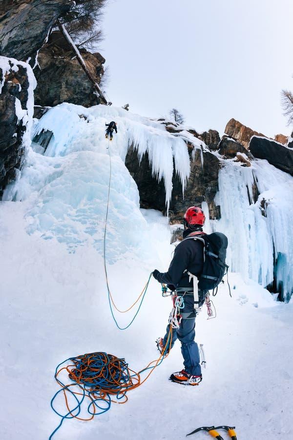 Альпинист belays руководитель во время взбираться льда стоковое изображение
