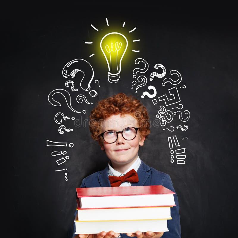 Бабочка и костюм мальчика нося с лампочкой и книгами на предпосылке классн классного Концепция метода мозгового штурма и идеи стоковое изображение