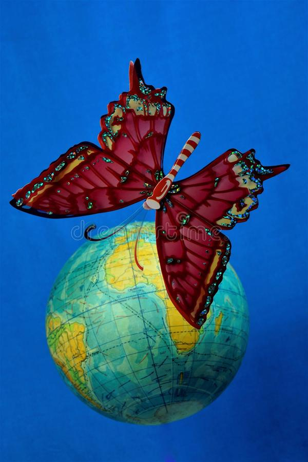 Бабочка летает в голубое небо над глобусом земли стоковое изображение rf