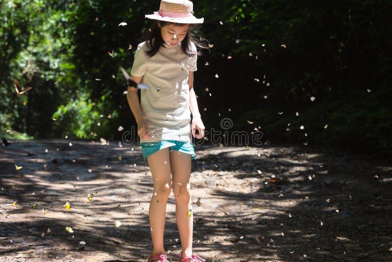 Бабочки группы летая вокруг молодой азиатской девушки, милой немного стоковые фото