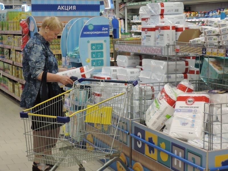 Бабушка выбирает пеленки для внуков в магазине Россия, Саратов - июнь 2019 стоковые фото