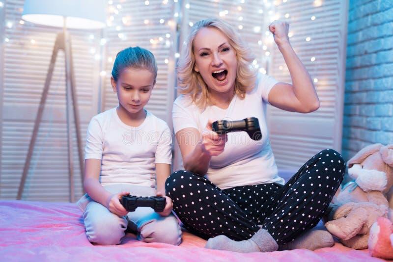 Бабушка и внучка играют видеоигры на ноче дома Женщина выигрывает стоковое изображение