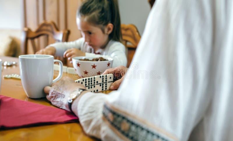 Бабушка и внучка играя домино стоковое фото