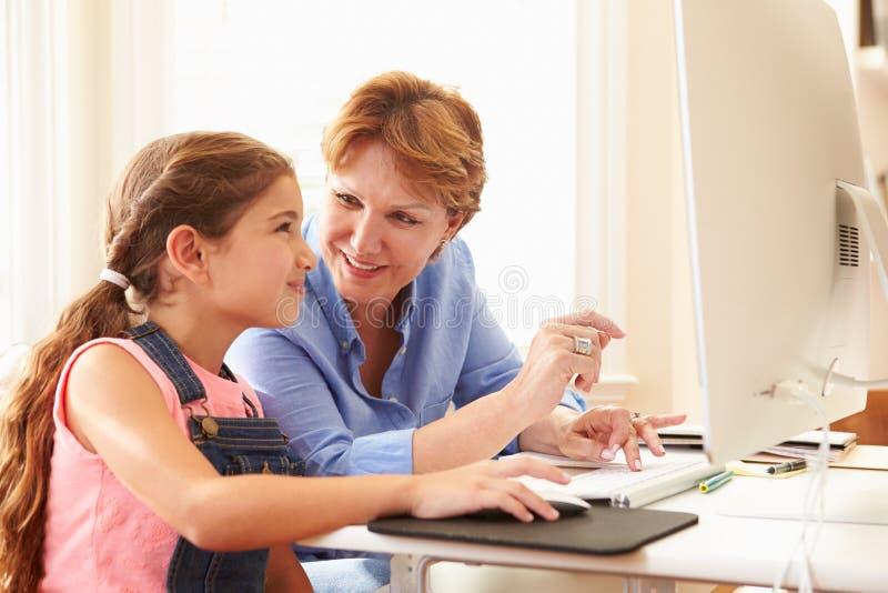 Бабушка и внучка используя компьютер дома стоковая фотография rf