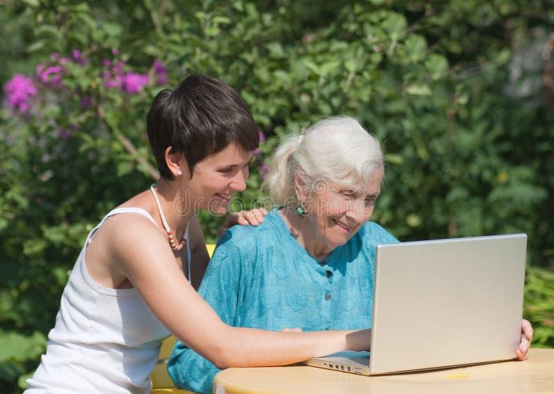 Бабушка и внучка с компьтер-книжкой стоковые изображения