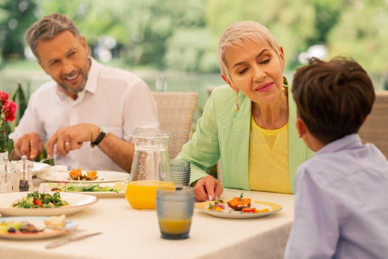 Бабушка позаботить об ее внук пока имеющ завтрак стоковые фотографии rf