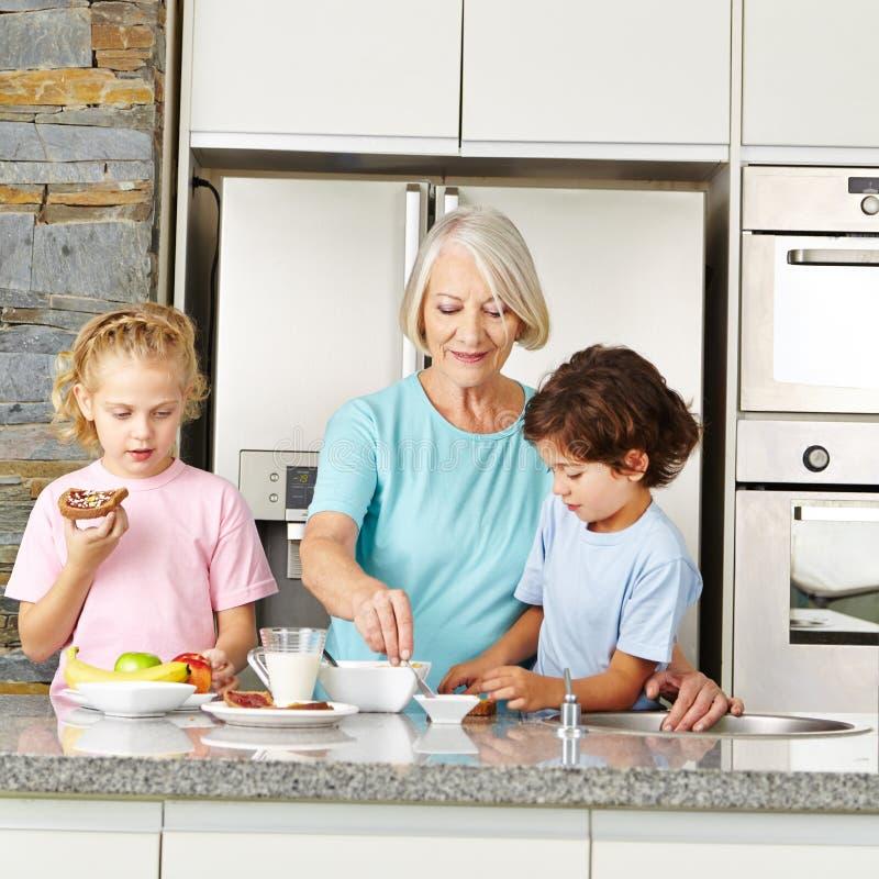 Бабушка подготавливая завтрак для детей стоковые фотографии rf
