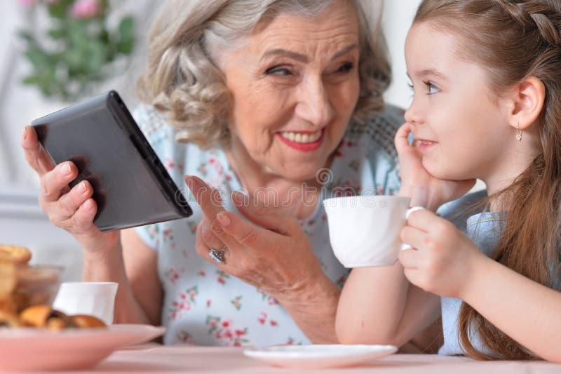 Бабушка при внучка играя в планшете стоковое изображение rf