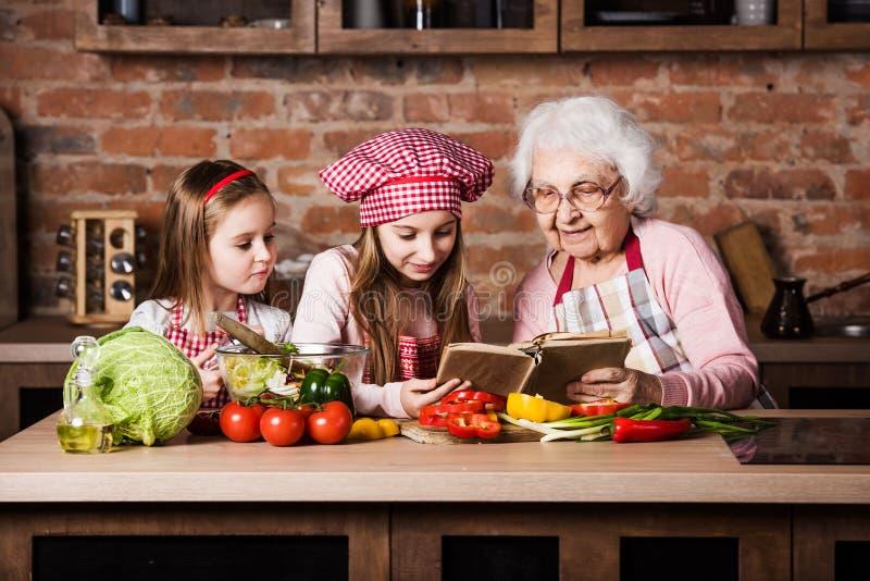 Бабушка при 2 внучки читая рецепт стоковые фотографии rf