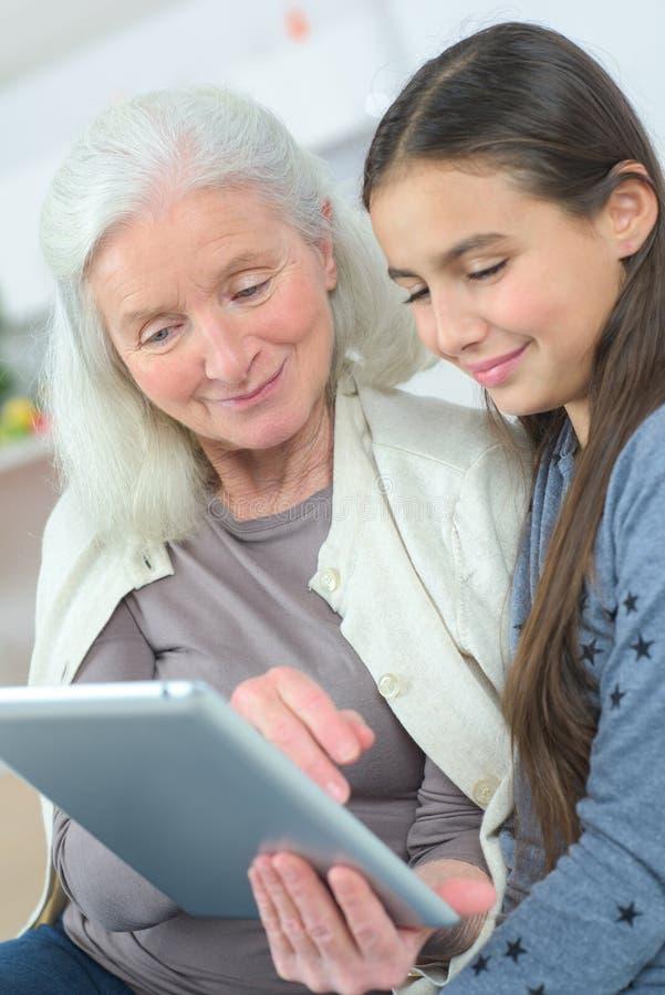 Бабушка при грандиозная дочь наблюдая что-то на таблетке стоковое фото