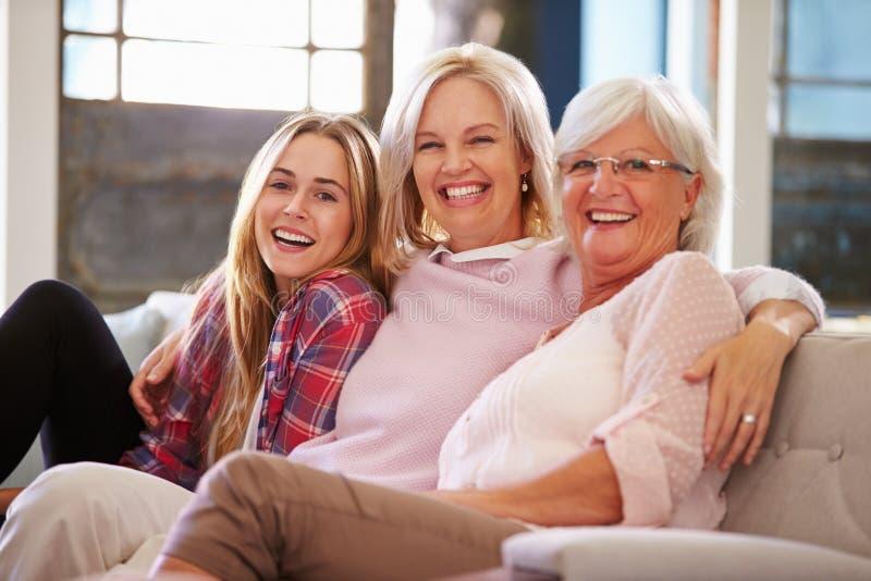 Бабушка при дочь матери и взрослого ослабляя на софе стоковое фото